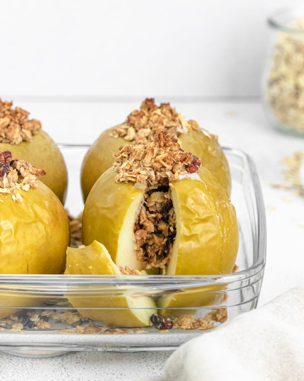 oatmeal stuffed breakfast baked apples sitting in a dish with a slice cut out to show the center.
