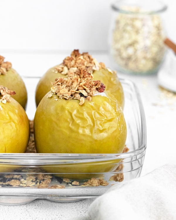 baked apples sitting in a glass casserole dish