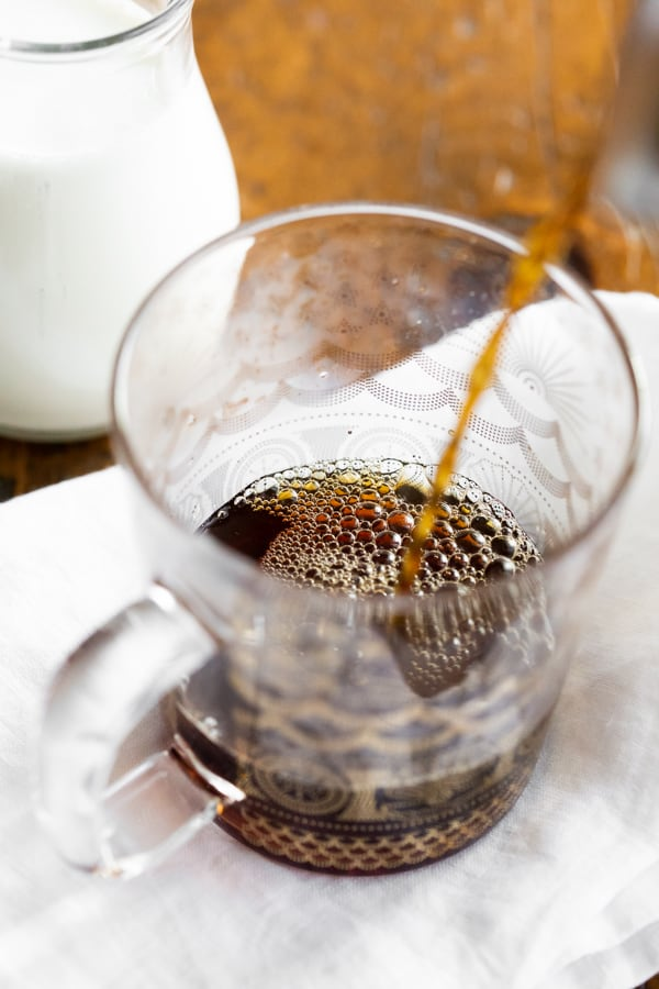 coffee being poured into a glass coffee mug