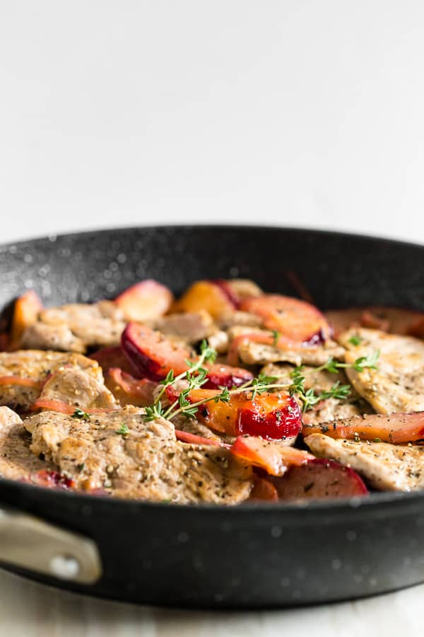 side shot of skillet pork tenderloin with plums
