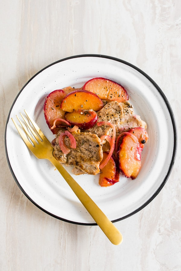 skillet pork tendrloin with plums shot from overhead on a plate with a fork.