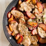 pork with plums in a skillet shot from overhead