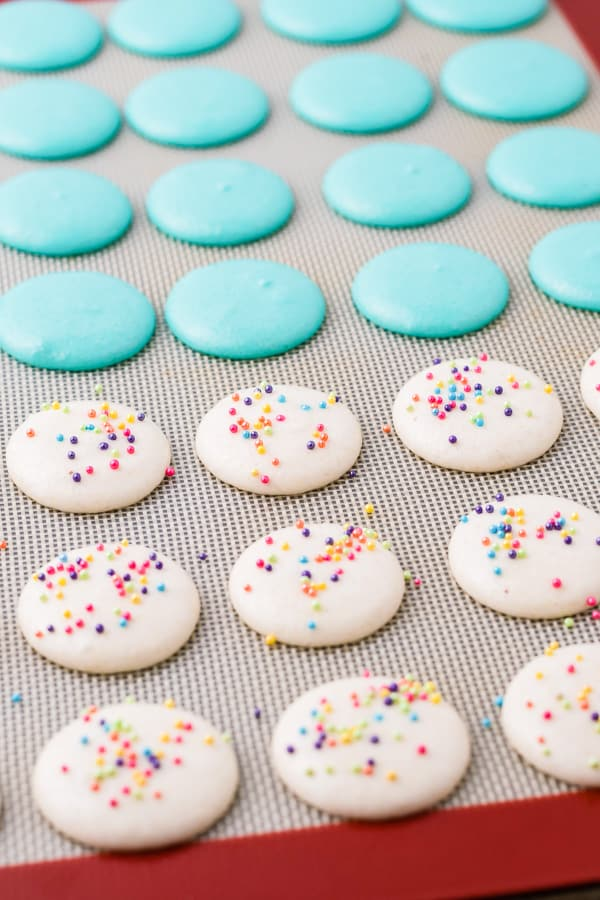 birthday cake macarons uncooked on a silpat liner