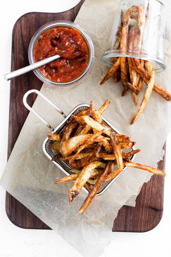Garlic Parmesan Air Fryer French Fries on a table with ketchup