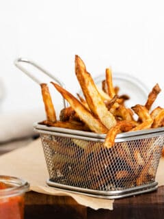 Garlic Parmesan Air Fryer French Fries in a metal basket
