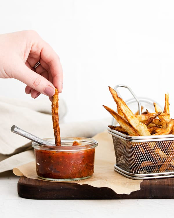 Garlic Parmesan Air Fryer French Fries being dipped into ketchup