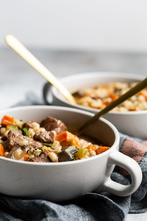 instant pot beef barley soup in a bowl with spoons