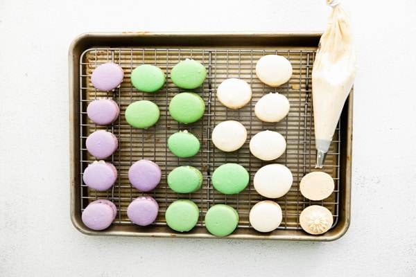Easter egg macarons on a sheet pan cooling