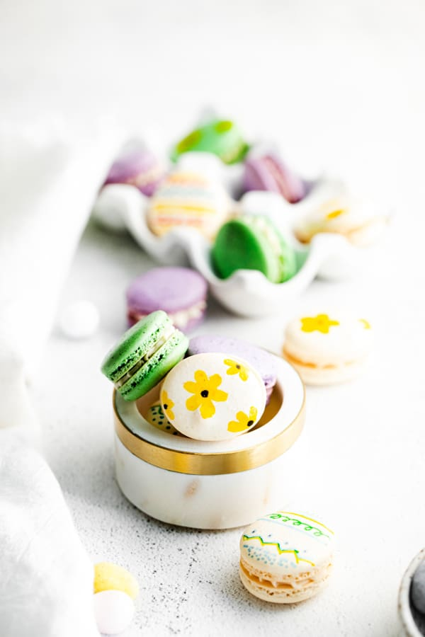 easter egg macarons in a white bowl.