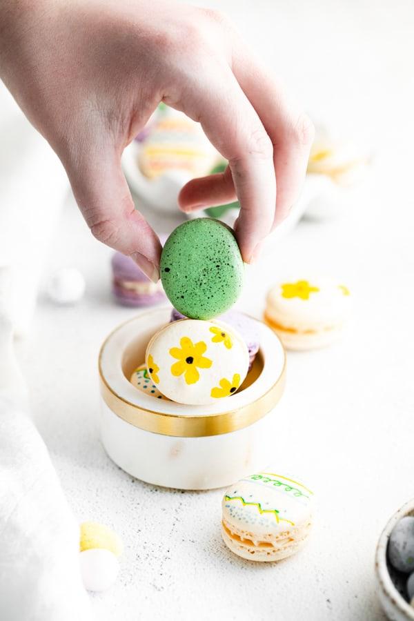 Holding a green easter egg macaron