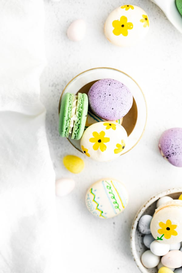 Easter egg macarons in a bowl decorated with flowers and speckled paint