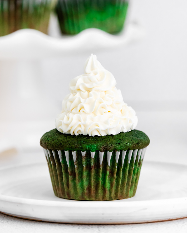 green velvet cupcake topped with vanilla frosting.