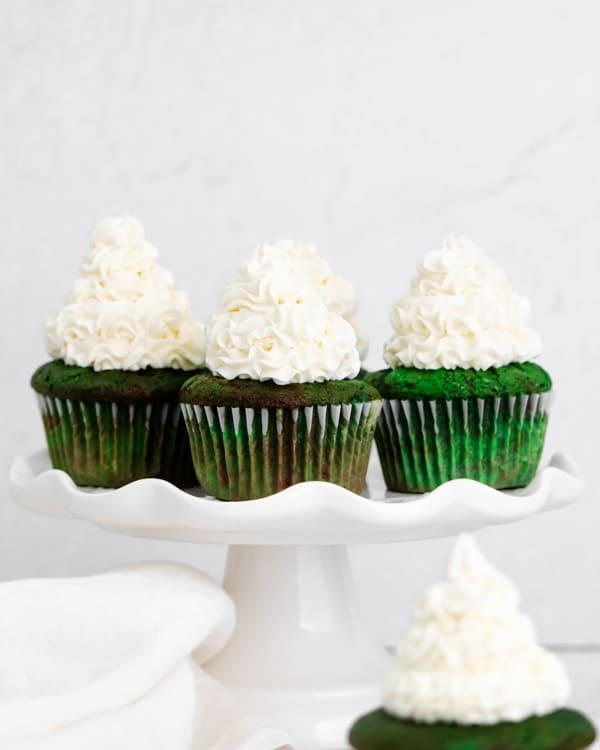 green velvet cupcakes on a cake plate.