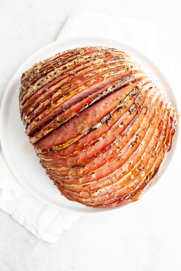 Honey Mustard Baked Ham covered and baked in glaze on a serving platter.
