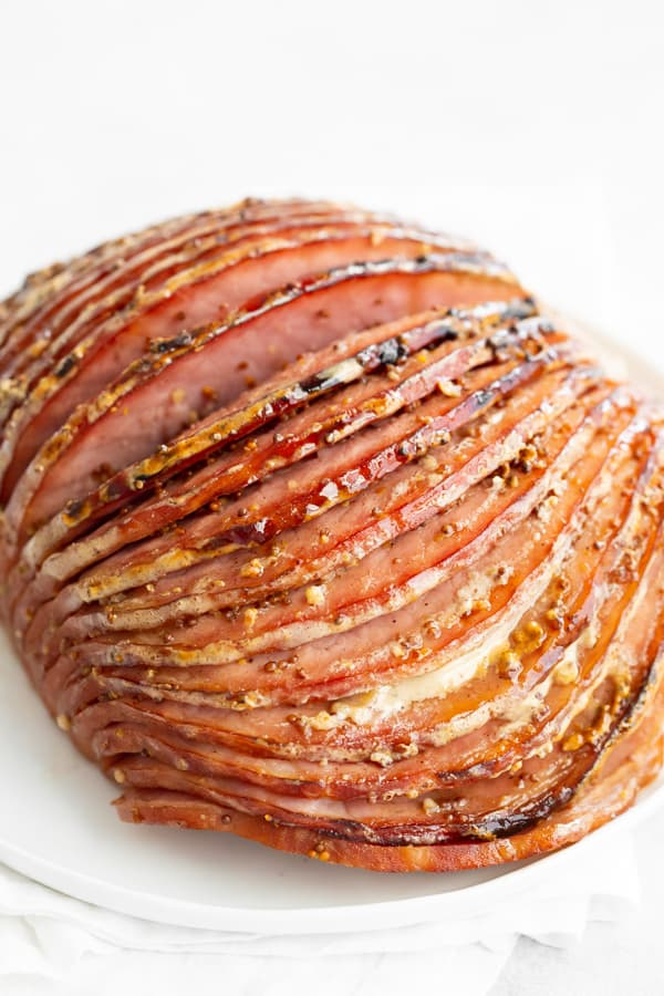 Honey Mustard Baked Ham with spiral slices showing on white plate.