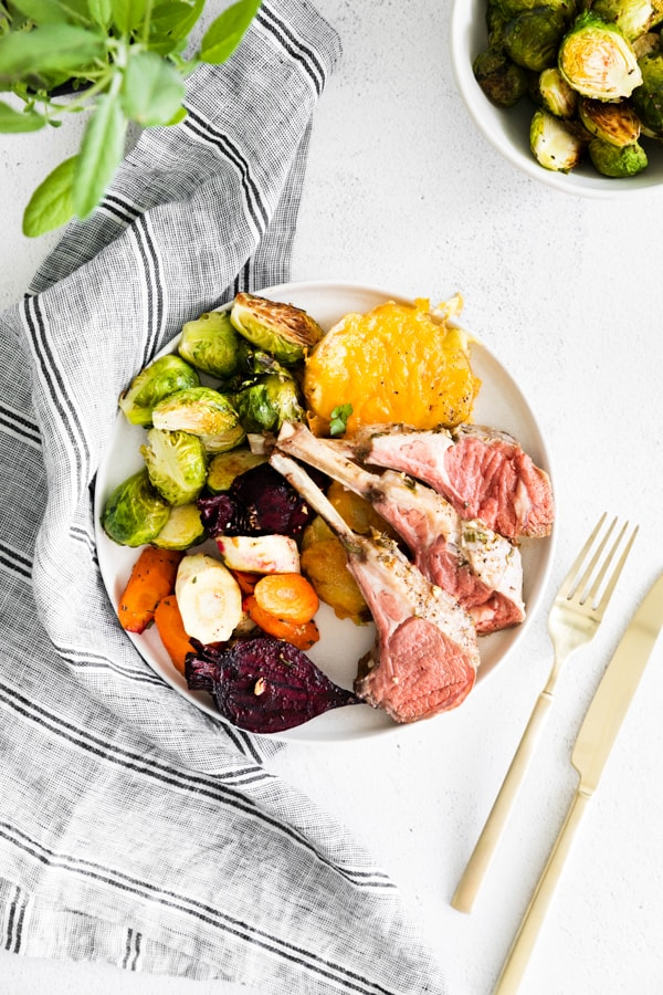 a plate with lamb chops, roasted vegetables, brussels sprouts, and scalloped potatoes.