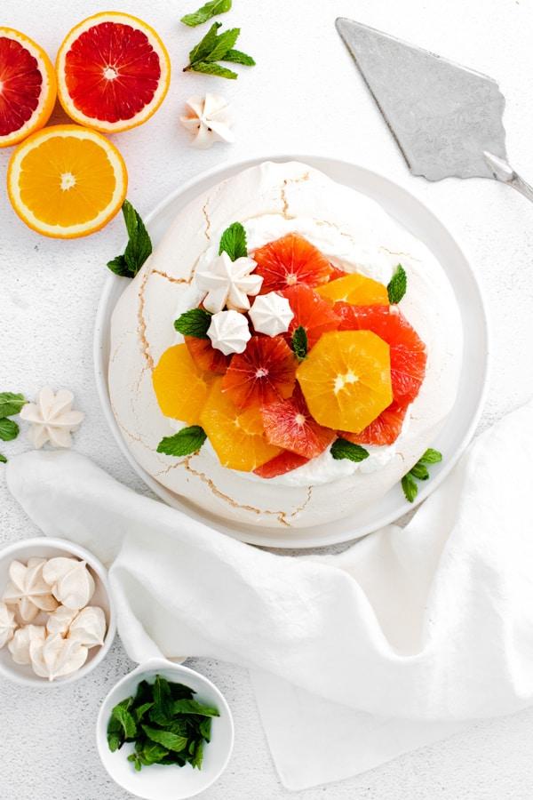 winter citrus pavlova sitting on a plate with a cake server.