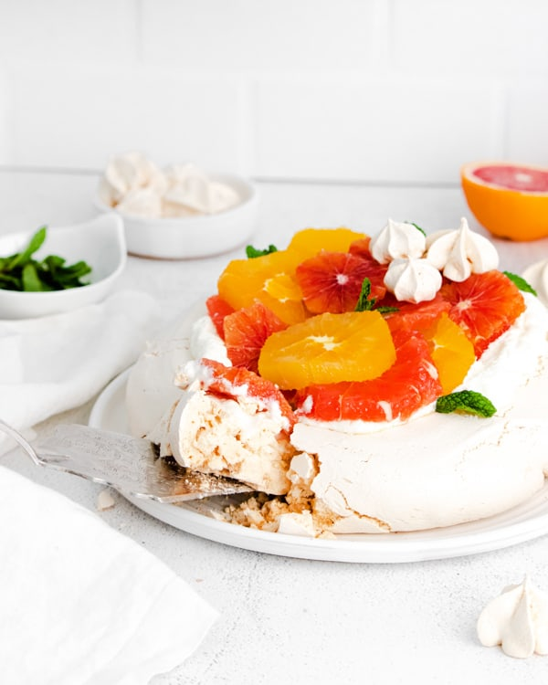 a slice being taken out of a winter citrus pavlova