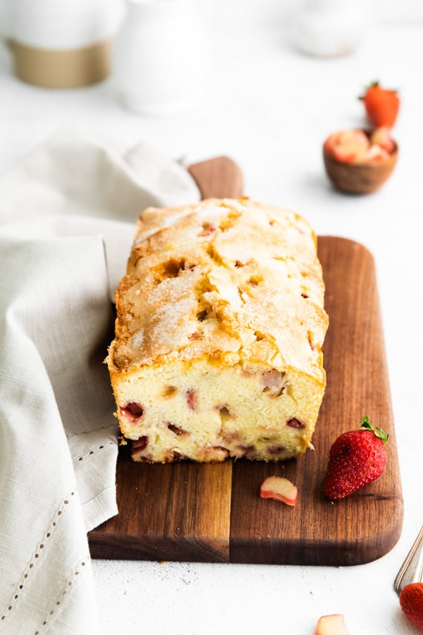 strawberry rhubarb pound cake on a serving board with fresh berries.