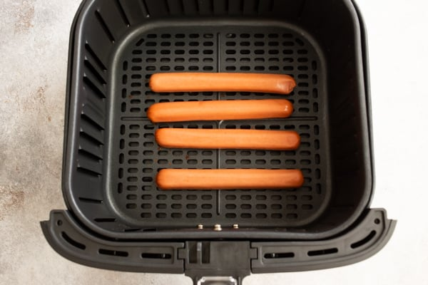 uncooked hot dogs in an air fryer basket.