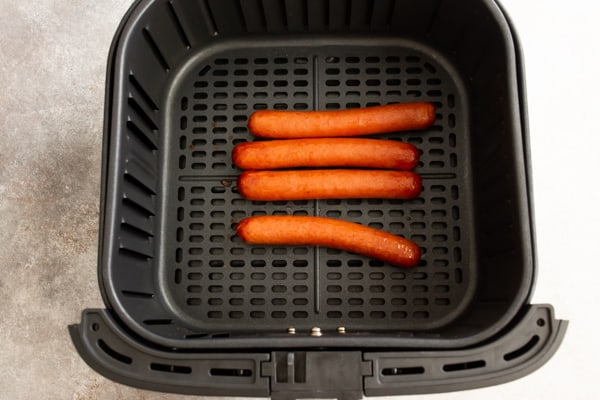 cooked hot dogs in an air fryer basket.