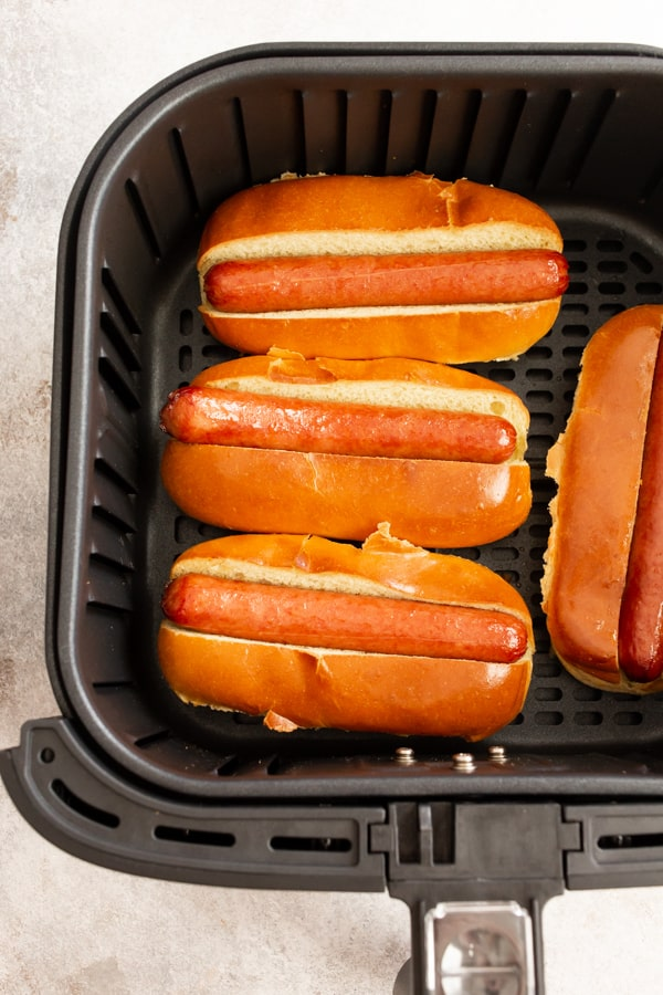 cooked air fryer hot dogs in an air fryer basket.