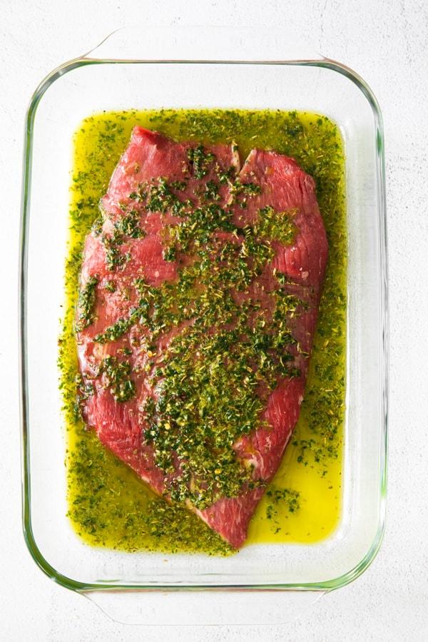 flank steak marinating in chimichurri sauce.