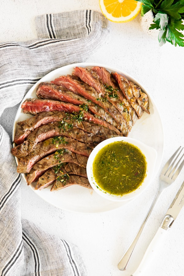 grilled chimichurri flank steak on a serving dish.