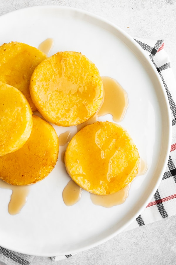 fried cornmeal mush on a plate with maple syrup.