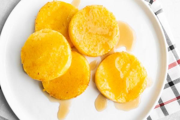 fried cornmeal mush on a white plate.
