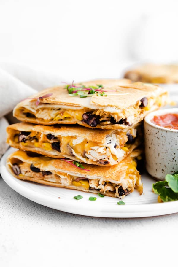 stacked sheet pan chicken quesadillas on a ceramic plate.