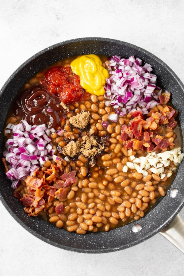 easy bacon baked beans in a skillet with all the ingredients on top before being mixed.