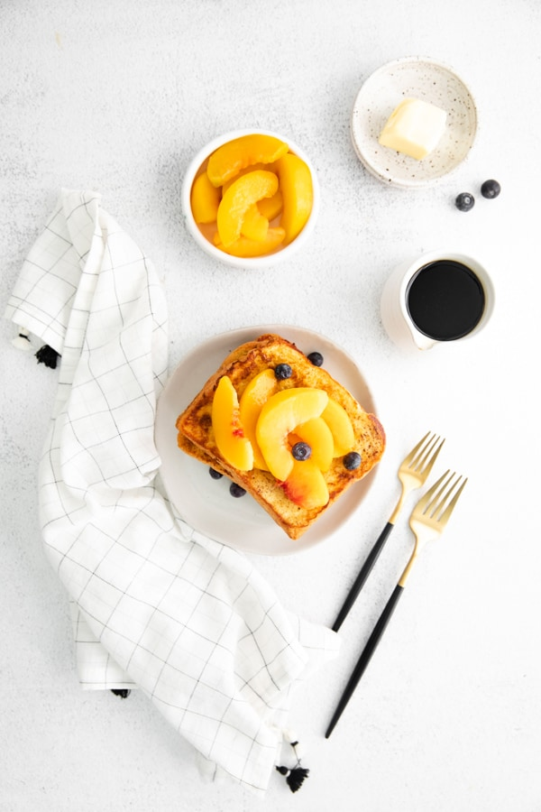Peach Topped French Toast on a white plate with forks.