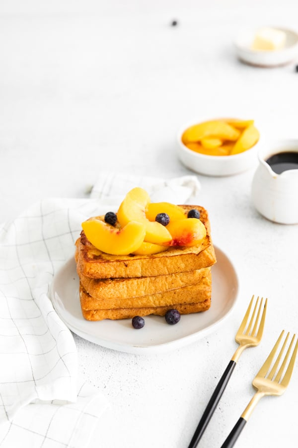 Peach Topped French Toast stacked on a plate.