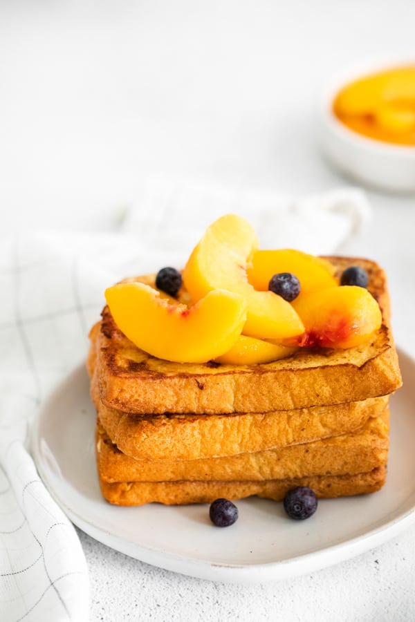 Peach Topped French Toast stacked on a plate topped with peaches and blueberries.