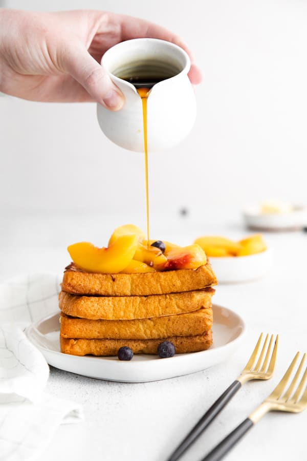 Peach Topped French Toast getting topped with syrup.