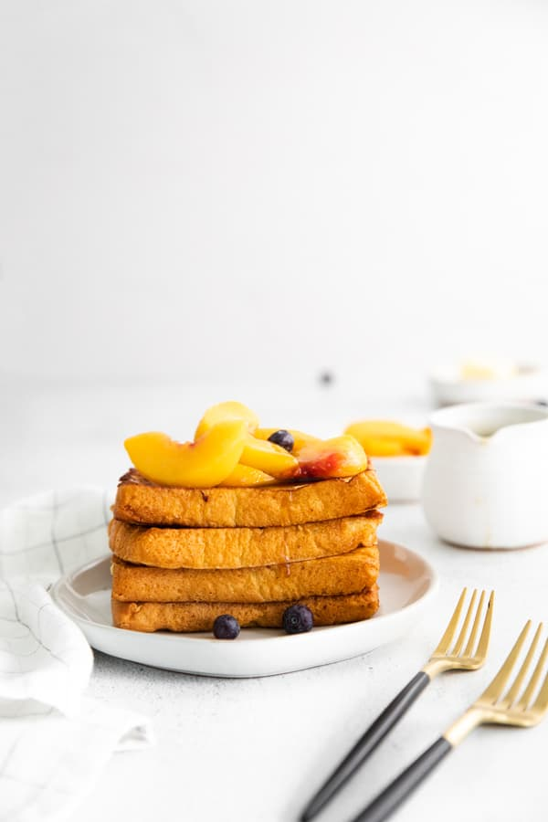 Peach Topped French Toast stacked on a plate topped with peaches and maple syrup.