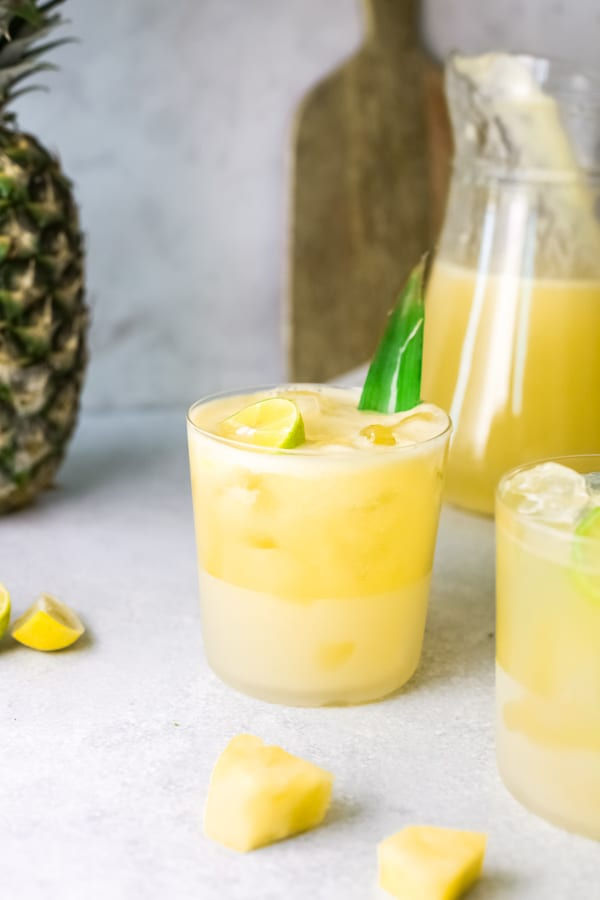 Pineapple Agua Fresca in a glass with a pitcher in the background.