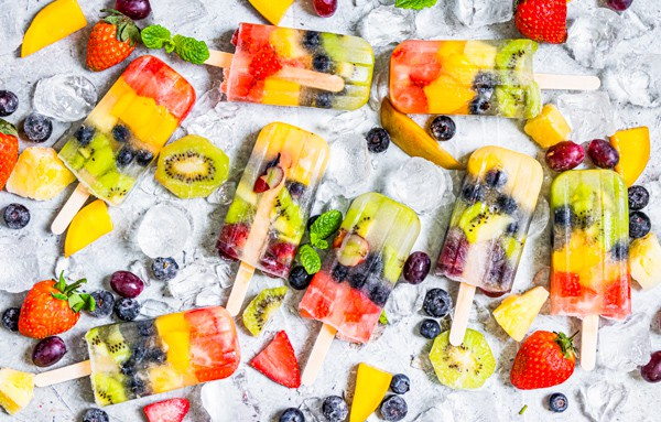 rainbow fruit popsicle on a serving tray with ice and lots of fresh fruit.