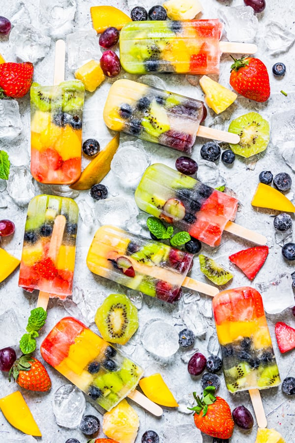 Rainbow Fruit Popsicles on a serving board with ice and fresh fruit.