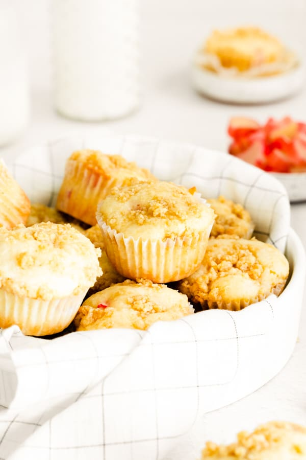 a basket of streusel topped rhubarb muffins.