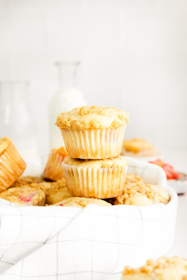 two streusel topped rhubarb muffins stacked on top of each other.