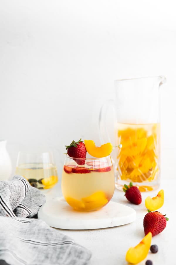 white wine peach sangria in a glass with peach slices and strawberries.