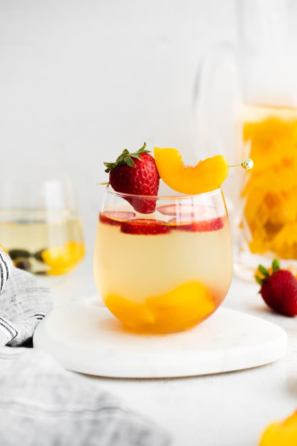 chilled white wine peach sangria in a serving glass.