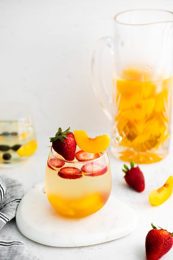 strawberries and peaches in a glass with white wine peach sangria.