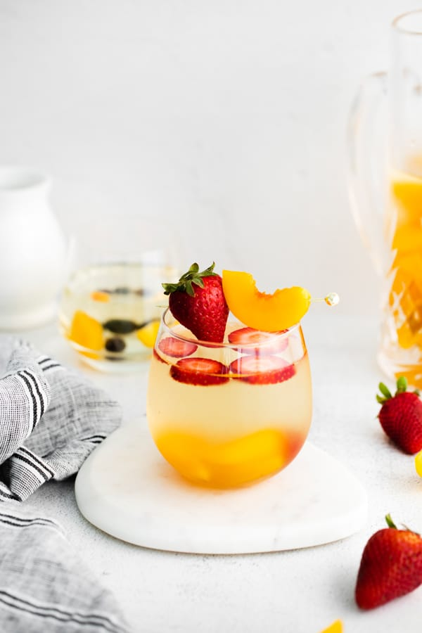 white wine peach sangria in a pitcher and in a serving glass.