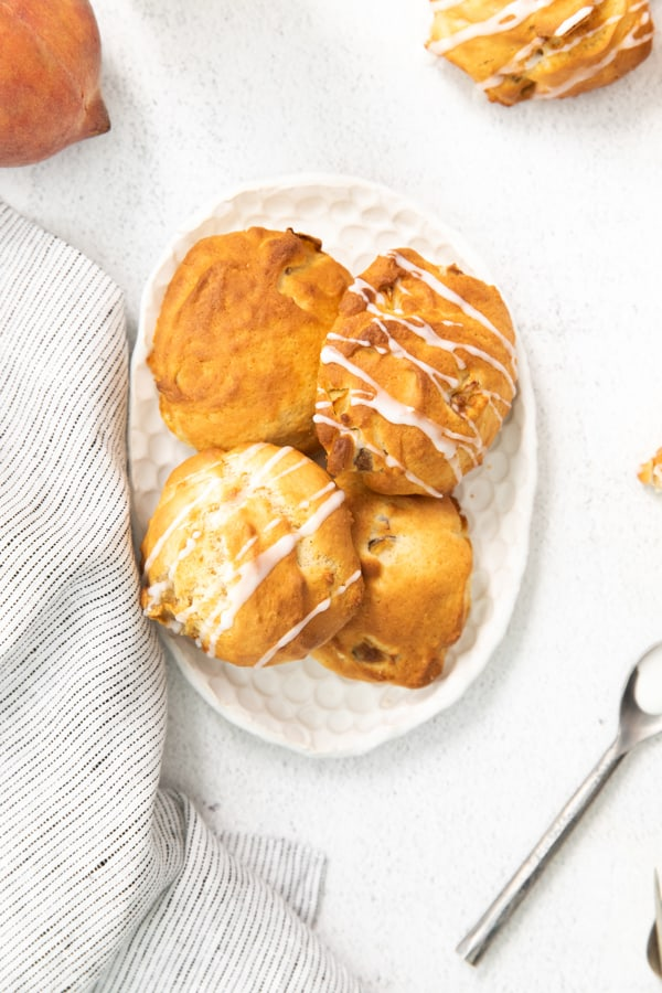 air fryer peach fritters drizzled with vanilla glaze.