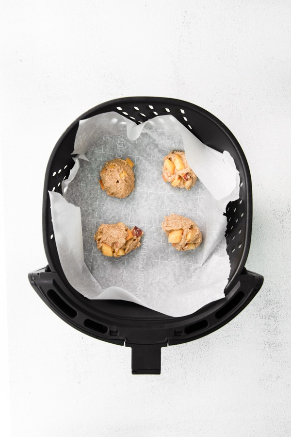air fryer peach fritters sitting in the air fryer waiting to be air fried.