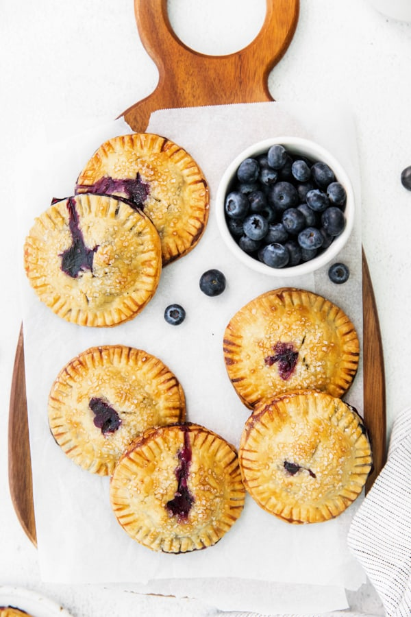 Easy Blueberry Hand Pies on a wooden serving tray.