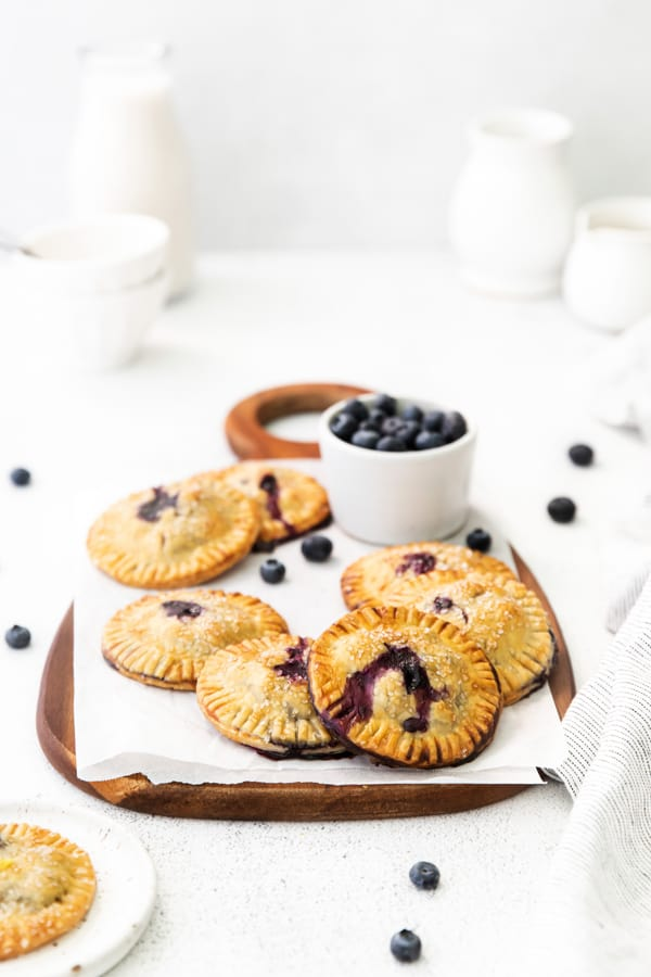 Easy Blueberry Hand Pies on a serving platter served with fresh blueberries.